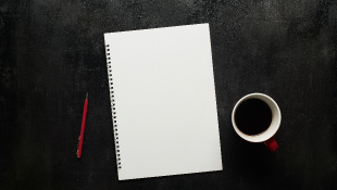 Notebook pen and coffee on black desk