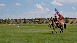 Horse rider with American flag riding over grass