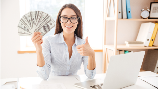 Woman holding cash in front of laptop