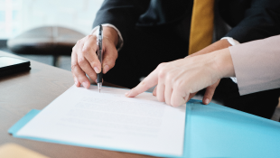 Businesswoman pointing at document for businessman to sign