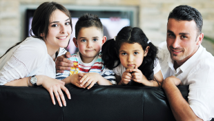Family leaning over back of couch
