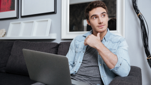 Businessman on couch with laptop looking pensive