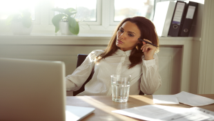 Businesswoman in home office in front of laptop