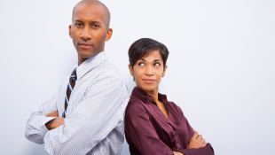 Two business people arms folded standing back to back