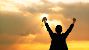 Businessman holding up both hands in victory gesture sunset background