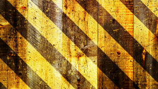 Construction stripes on wooden background