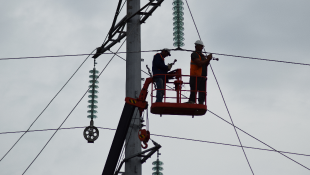Construction workers on crane repairing power lines