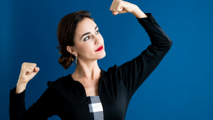 Businesswoman with arms raised powerfully