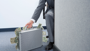 Businessman holding silver suitcase bulging with cash