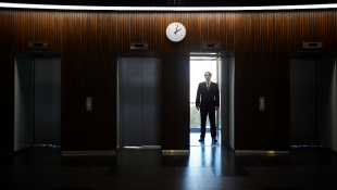 Businessman standing in darkened room