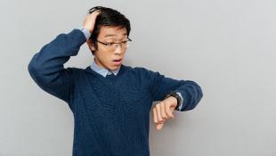 Asian man looking at watch