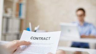 Businessmember holding contract with person in background