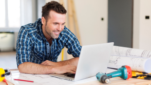Man sitting at laptop with construction tools on table