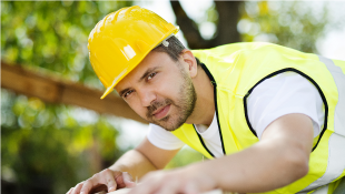 Construction worker working with wooden beam