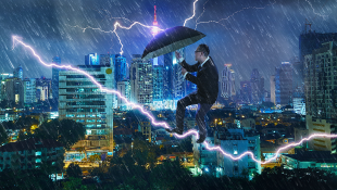 Businessman holding umbrella challenging storm in urban environment