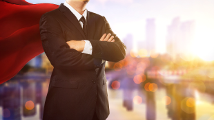 Businessman with red cape and arms folded in superhero stance