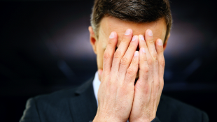 Businessman with hands covering face
