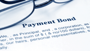 Glasses lying on Payment Bond document