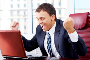 Businessman in triumph in front of laptop