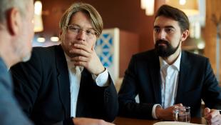 Three businessmen sharing ideas, looking pensive