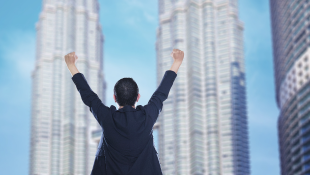 Businessman with hands up in triumph