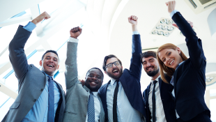 Team of business people raising their arms in triumph