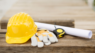 Hardhat gloves measuring tape and plans resting on wooden table