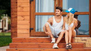 Couple sitting in front of house