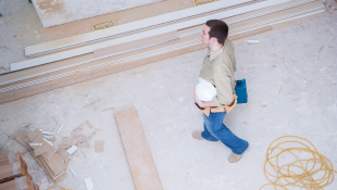 Construction worker holding plans walking through building
