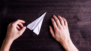 Hands on desk holding paper airplane
