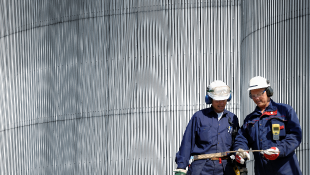 Two construction workers standing in front of metal building