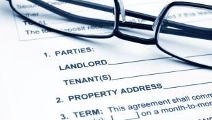 Glasses lying on Landlord-Tenant agreement