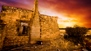 Sun sets over old ruined building
