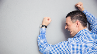 Businessman with fists against grey wall