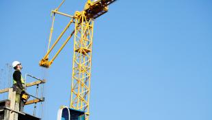 Construction worker operating crane
