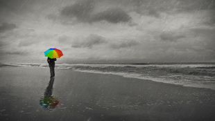 Businesswoman holding umbrella on beach
