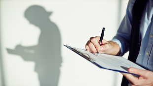 Businessman with clipboard signing document