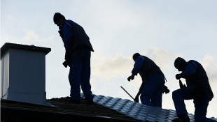 Three contractors on roof making repairs