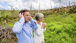 Senior couple staring at hurricane damage