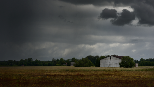 storm clouds over rural house and field