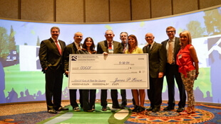 Group holding oversized BHA donation check presented at WCC Seminar
