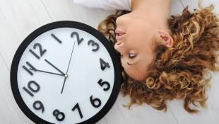 Woman lying beside clock