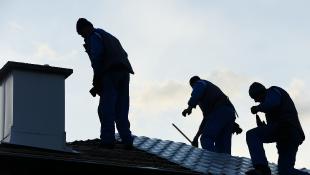 Three contractors repairing roof