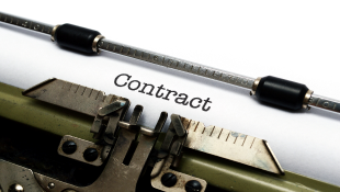 Contract on white paper in typewriter
