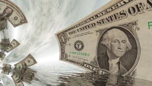 Dollar Bills swirling in the sky with ocean below