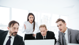Four business people around computers looking shocked