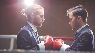 Two men in suits in boxing ring pressing gloves together